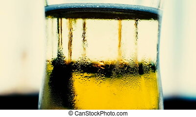 Clear glass with yellow bubbling soda water.