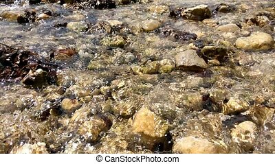 Clear mountain cold water flows over stones in the sun....