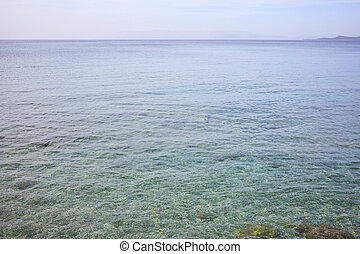 Clear sea surface. Shallow water, blue sky background