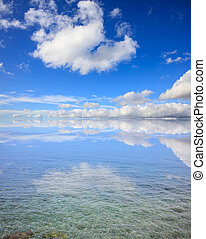 Clear sea surface. Shallow water, blue sky with clouds background