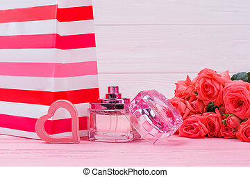 Clear shopping bag with perfume bottle and rose flowers.