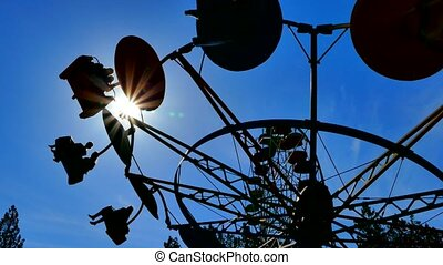 Clear sky, the silhouette of a spinning carousel - The clear...