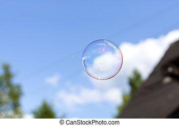 Clear soap bubble in blue sky