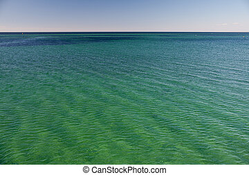 clear turquoise green blue water with little waves under blue sky