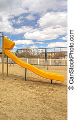Clear Vertical Playground with slides and swings under the blue sky filled with puffy clouds