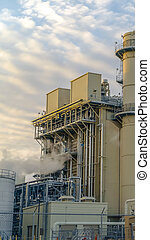 Clear Vertical Power Plant releasing steam against pale blue sky with bright puffy clouds