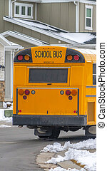 Clear Vertical Rear view of a yellow school bus running on a road with fresh snow in winter
