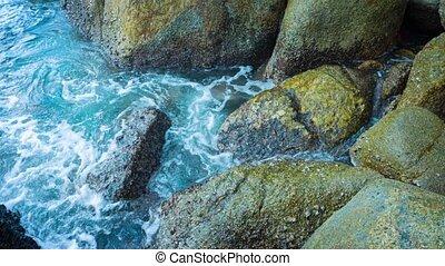 Clear Water Sloshing onto Big Mossy Rocks