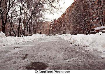 Cleared path in the yard of the house in a residential area. Heavy snowfall in the city.