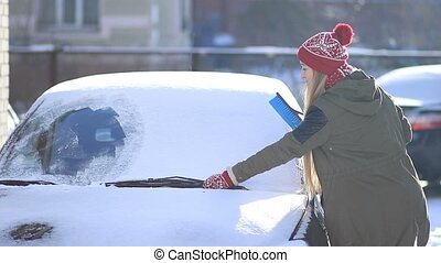 Clearing automobile's windscreen from snow - Young beautiful...