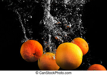 Clementines falling in water