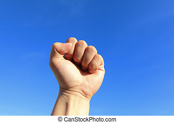 Clenched fist in the air with blue sky