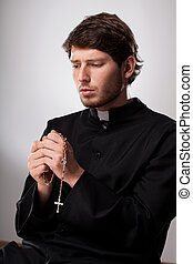 Cleric praying with a  rosary after confession