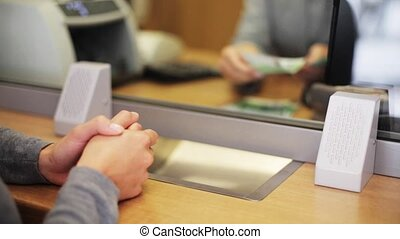 clerk counting money and customer at bank office - people,...