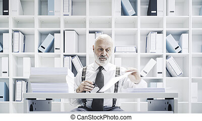 Senior corporate clerk doing a boring job in the office, he is stamping paperwork