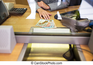 clerk with cash money at bank office or exchanger