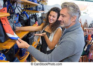 Clerk with customer in bag shop