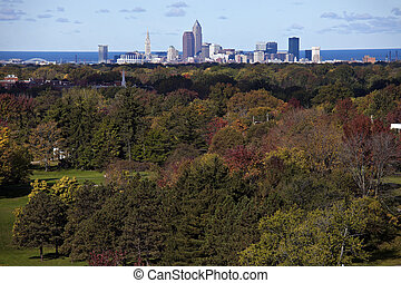 Cleveland - distant skyline view with colorful trees in the foreground.