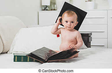 Clever baby boy in graduation cap posing with books