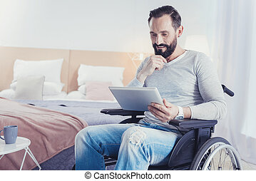 Clever blogger sitting in a wheelchair and looking at the screen of his device