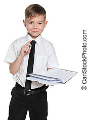 Clever boy in white shirt with a notebook