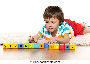 Clever boy with blocks on the carpet