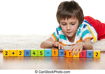 Clever boy with blocks on the floor