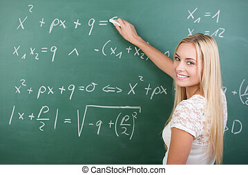 Clever confident female student in the classroom writing on...