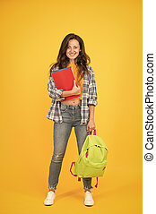 Clever forever. Girl student yello background. Happy girl back to school. Pretty girl borrow books in library. Smart girl smile in casual wear. Education and learning. Knowledge and skills