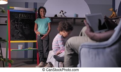 Dark-skinned man with tablet having a lesson and encouraging daughter to learn english words. Caring dad studying with schoolgirl at home, preschooler playing on bed
