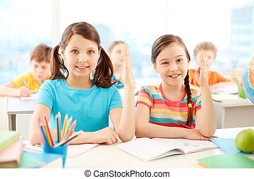 Clever girls - Portrait of two diligent girls raising hands ...