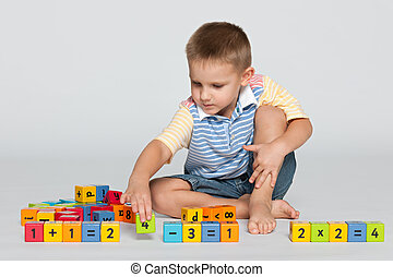 Clever little boy with blocks on the floor