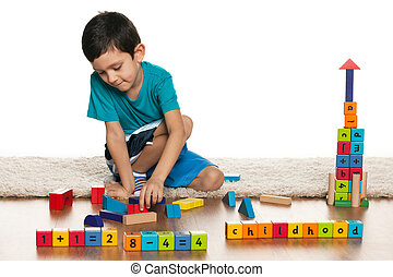 Clever little boy with toys on the floor