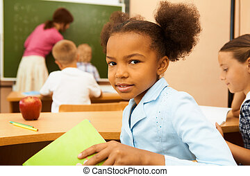 Portrait of cute girl looking at camera at workplace during lesson