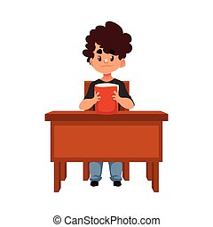 Clever school boy sitting at the desk, holding a book