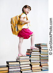 View from aside of smart girl going upwards on book stairs