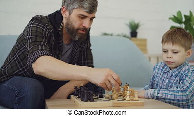 Clever small boy is playing chess with his caring father...