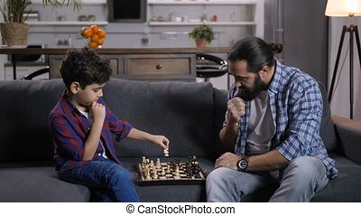 Clever son moving knight piece during chess game -...