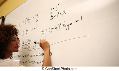 Clever student solving math problems on whiteboard at the...