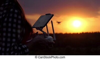Clever woman keeps a panel to operate her drone at sunset in slo-mo