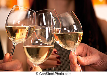 Clicking glasses with white wine. - Clinking glasses with...