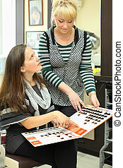 Client and hairdresser look catalog of hair colors and choose appropriate color in beauty salon