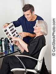 Client And Hairdresser Selecting Hair Color From Catalog -...