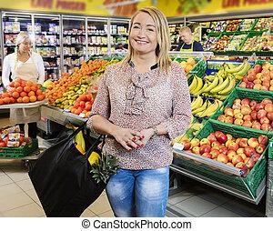 client, debout, épicerie, magasin, fruits, frais, heureux