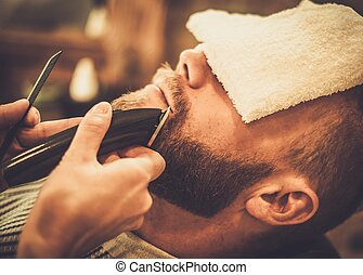Client during beard and moustache grooming in barber shop