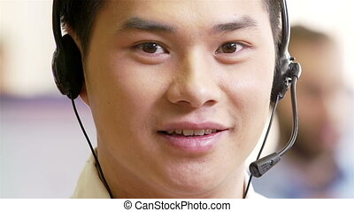 Client help-desk - Asian man using headset talking to a...