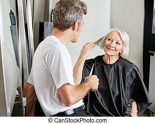 Senior female client instructing male hairdresser in beauty salon