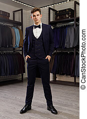 client is elegant guy trying on a suit in a mirror shop. In the background classic suits and jackets