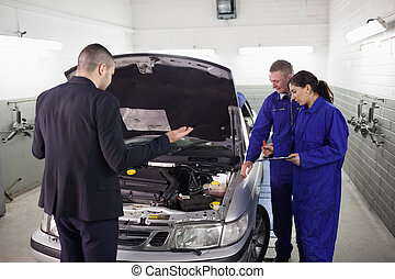Client looking at a car engine
