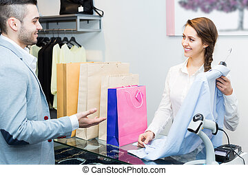 Client paying for new apparel at store - Positive smiling...